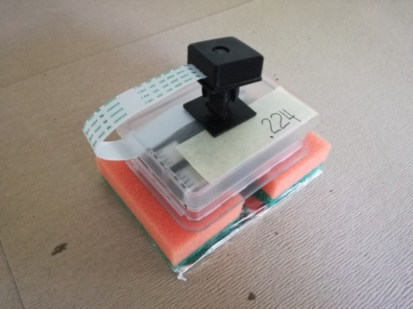 Raspberry Pi (computador de placa reducida) con módulo de cámara. Esta unidad puede ser montada en el techo de un aviario para capturar imágenes en áreas específicas. En la foto puede verse el montaje utilizado para disipar el calor, ya que fue utilizado en un aviario expuesto al sol, causando el sobrecalentamiento del Raspberry Pi.